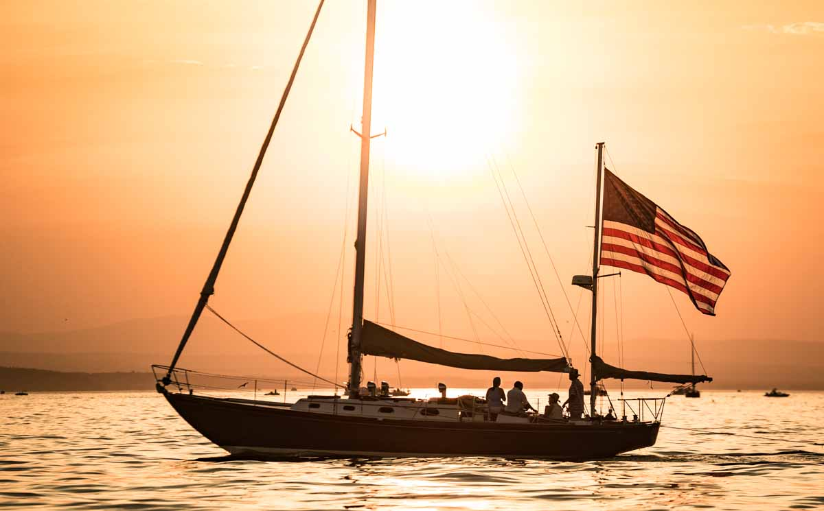 sailboat with flag with bright orange sunset - metaphor for website remediation